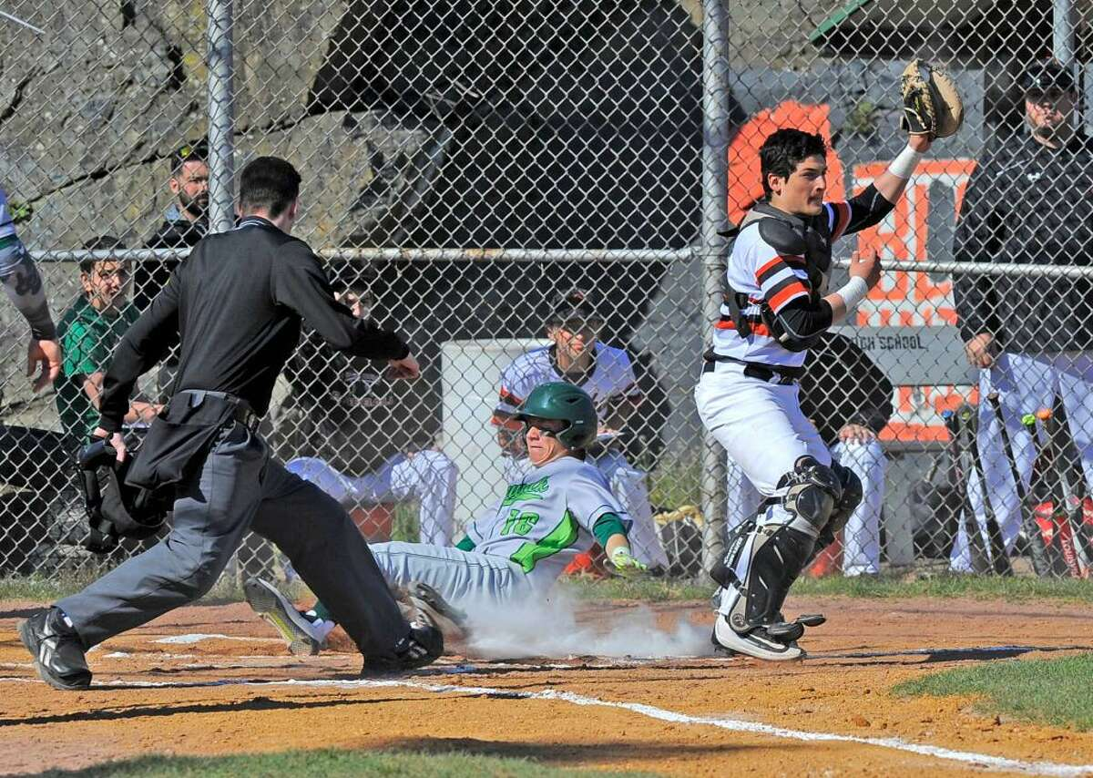 Norwalk Eddie McCabe slides past Stamford catcher Nico Kydes scoring in the first inning of a FCIAC boys baseball game at Stamford High School on April 15, 2016. Norwalk defeated Stamford 8-7.
