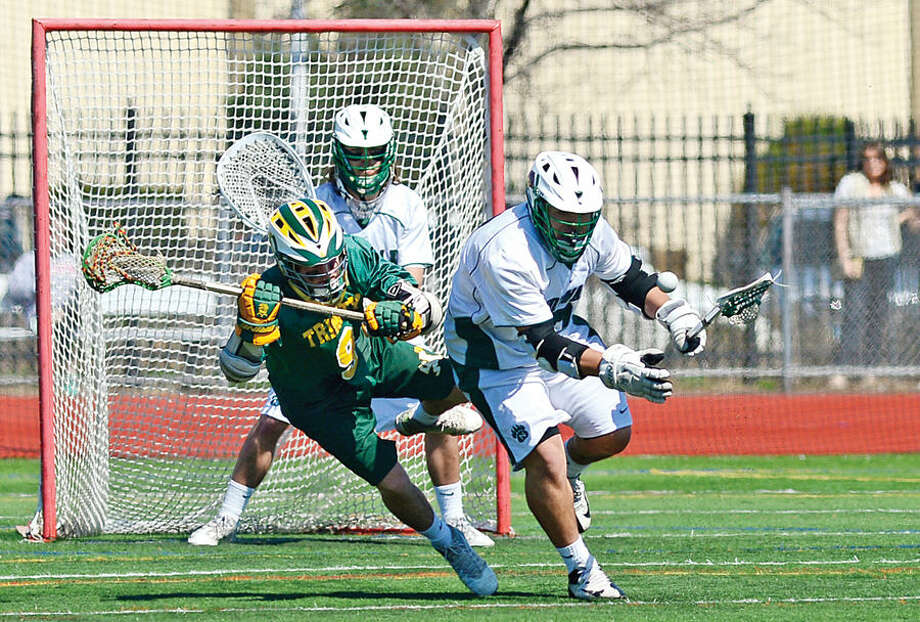 Hour photo / Erik Trautmann Norwalk's #3 Adriyel Ibarrondo during battles Trinity Catholic 's #9 Conor Ehring their lacrosse game Saturday