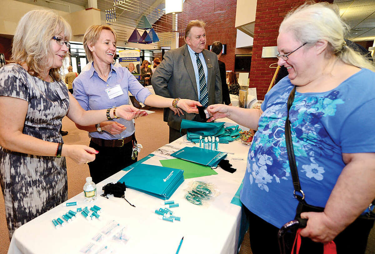 Hour photo / Erik Trautmann First County Bank employees Andrea Kusnierikova and Grazyna Maciejewska hand out give-aways to Judith Herman during the Norwalk Leadershp Institute Senior Expo Project at the Norwalk Community College where over 25 tables were hosted by local non profit and for profit organizations that provide critical services to Norwalk seniors.