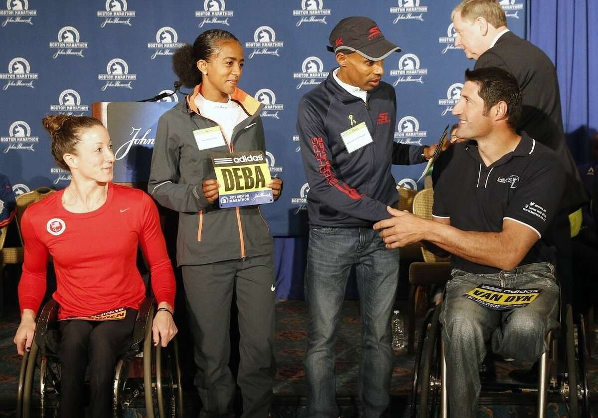 Ernst van Dyk, right, of South Africa, shakes hands with Meb Keflezighi, second from right, as Buzunesh Deba, second from left, of Ethiopia, and Tatyana McFadden, left, look on during a news conference in Boston, Friday, April 17, 2015. The 119th Boston Marathon will be run on Monday. (AP Photo/Michael Dwyer)