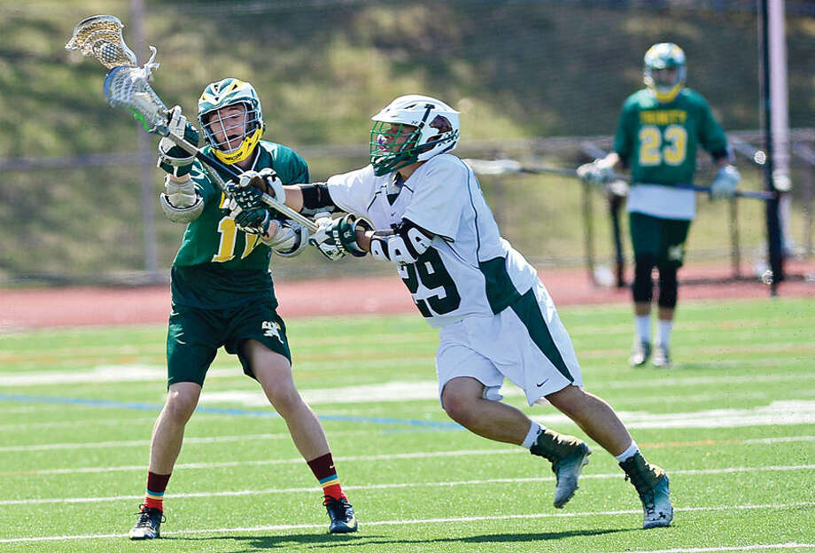Hour photo / Erik Trautmann Norwalk's #29 Cody Mastropietro battles #10 Joey Nelson during their lacrosse game against Trinity Catholic Saturday