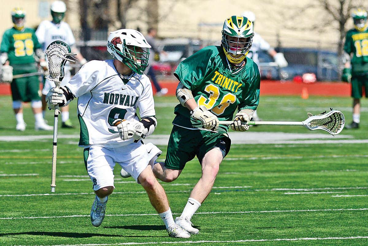 Norwalk's Zachary Grimm keeps the ball away from Trinity Catholic's Liam Shanahan on Saturday. (Hour photo / Erik Trautmann)