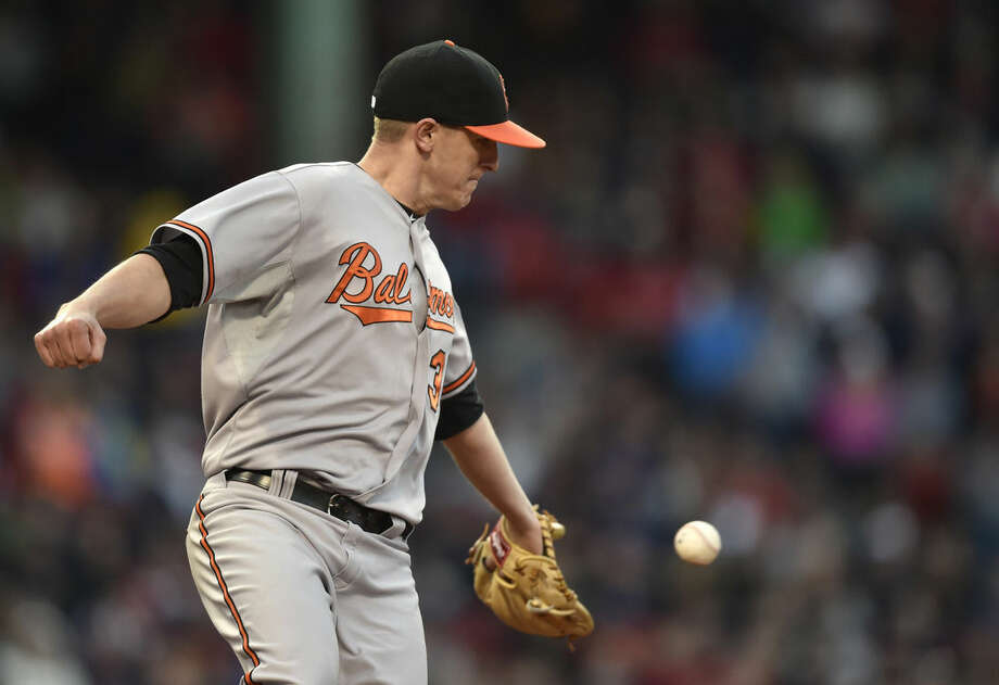 Baltimore Orioles relief pitcher Brad Brach reaches for the ball as he runs toward first after a hit by Boston Red Sox's Brock Holt in the seventh inning of a baseball game, Saturday, April 18, 2015, in Boston. (AP Photo/Gretchen Ertl)