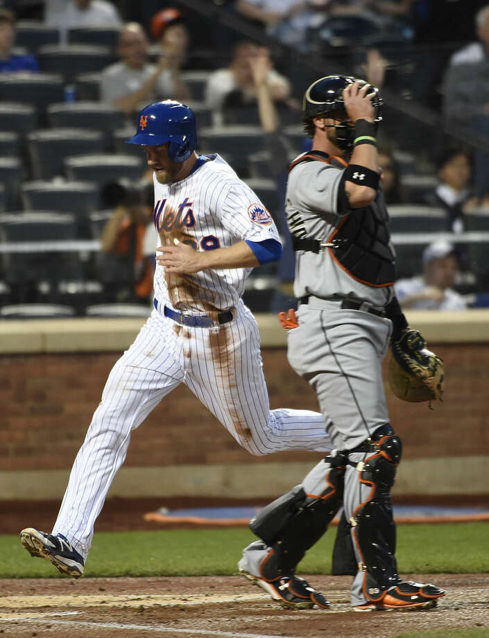 New York Mets' Eric Campbell, left, scores at home plate behind Miami Marlins catcher Jarrod Saltalamacchia on an RBI-single by Juan Lagares in the second inning of a baseball game at Citi Field on Saturday, April 18, 2015, in New York. (AP Photo/Kathy Kmonicek)