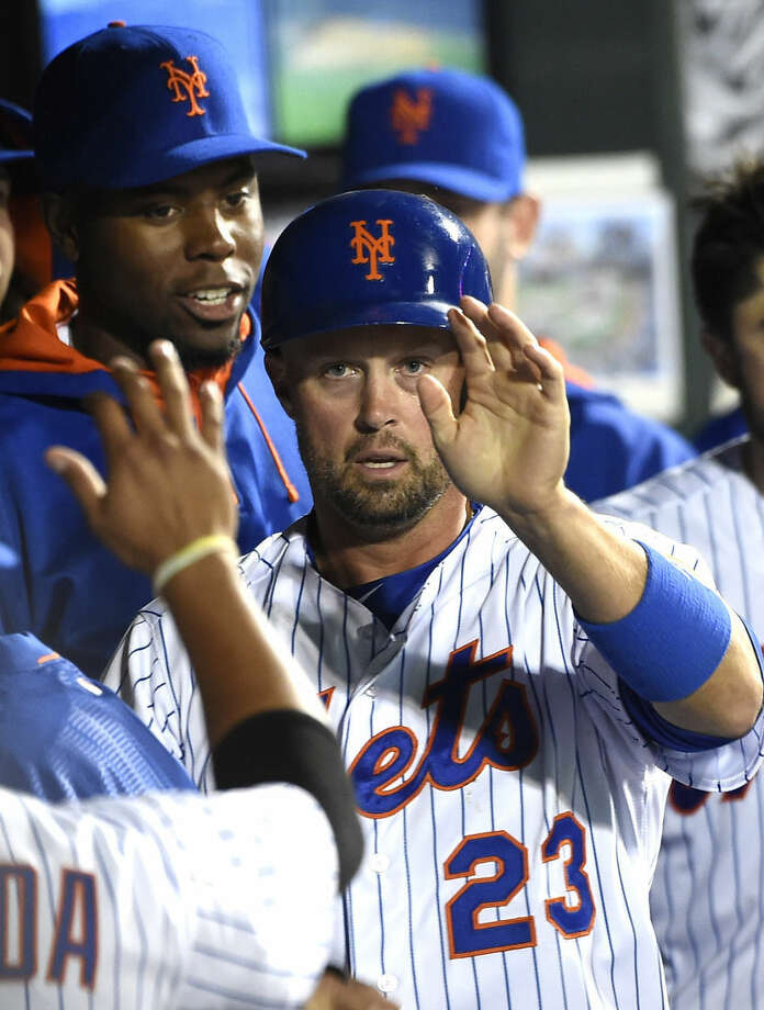 New York Mets Michael Cuddyer (23) is greeted in the dugout after scoring on Eric Campbell's single in the sixth inning of a baseball game against the Miami Marlins at Citi Field on Saturday, April 18, 2015, in New York. (AP Photo/Kathy Kmonicek)