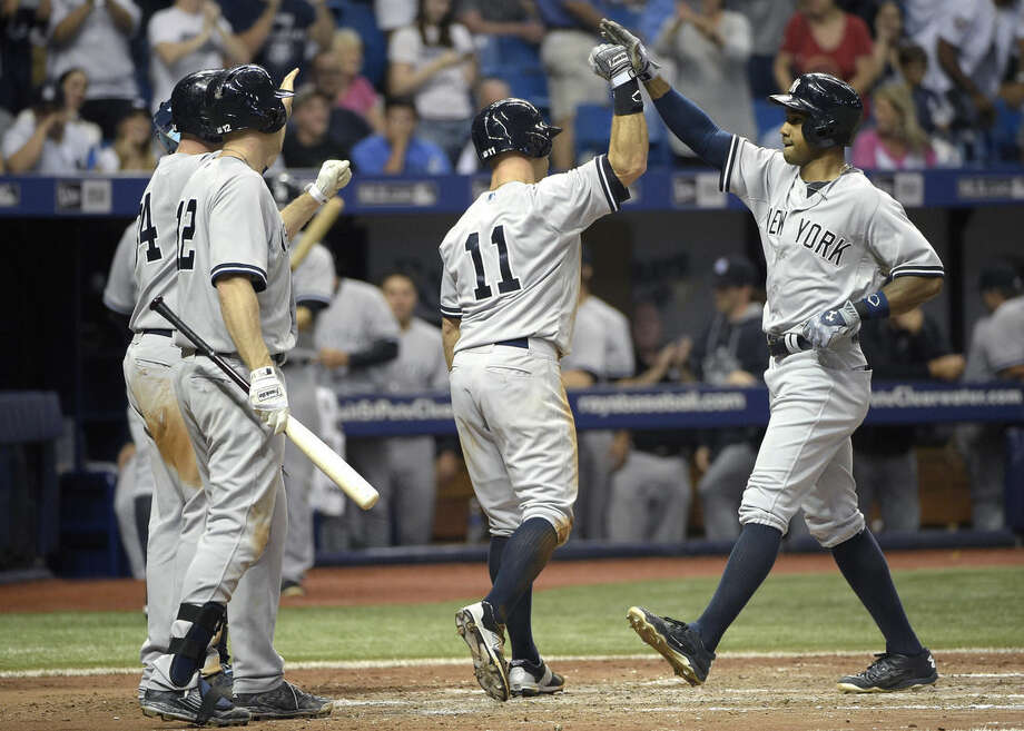 New York Yankees' Chris Young, right, is congratulated by Brian McCann, left, Chase Headley (12) and Brett Gardner (11) after hitting a grand slam during the seventh inning of a baseball game against the Tampa Bay Rays in St. Petersburg, Fla., Saturday, April 18, 2015.(AP Photo/Phelan M. Ebenhack)