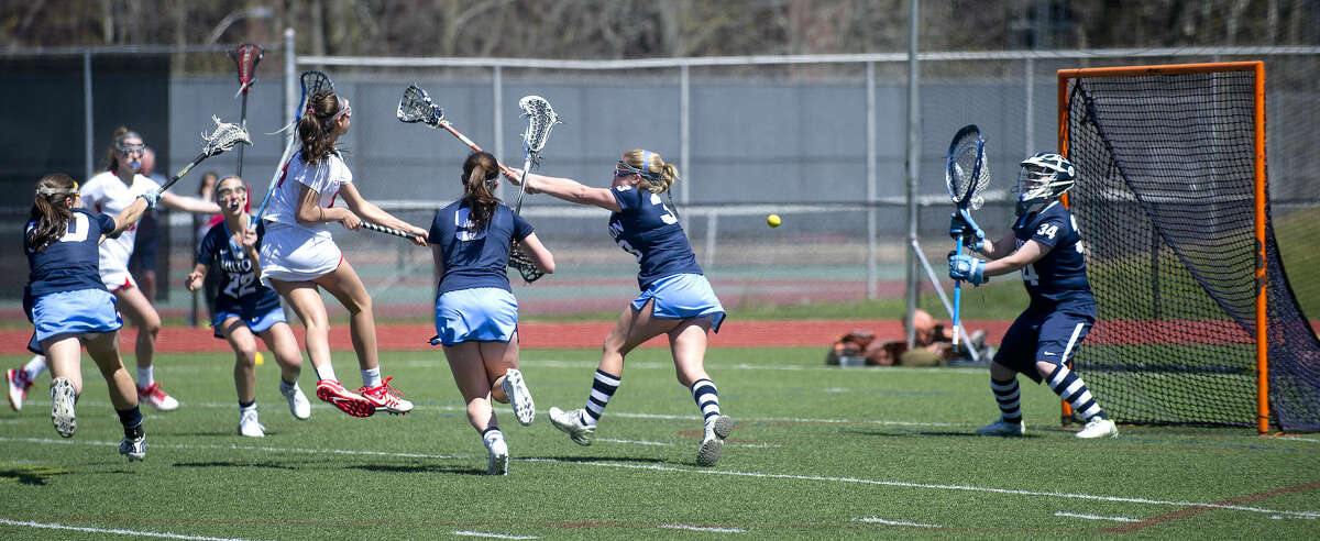 Greenwich's Genevieve DeWinter takes a shot as Wilton's Bridette Wall tends goal during Saturday's girls lacrosse game against Wilton at Greenwich High School on April 16, 2016.