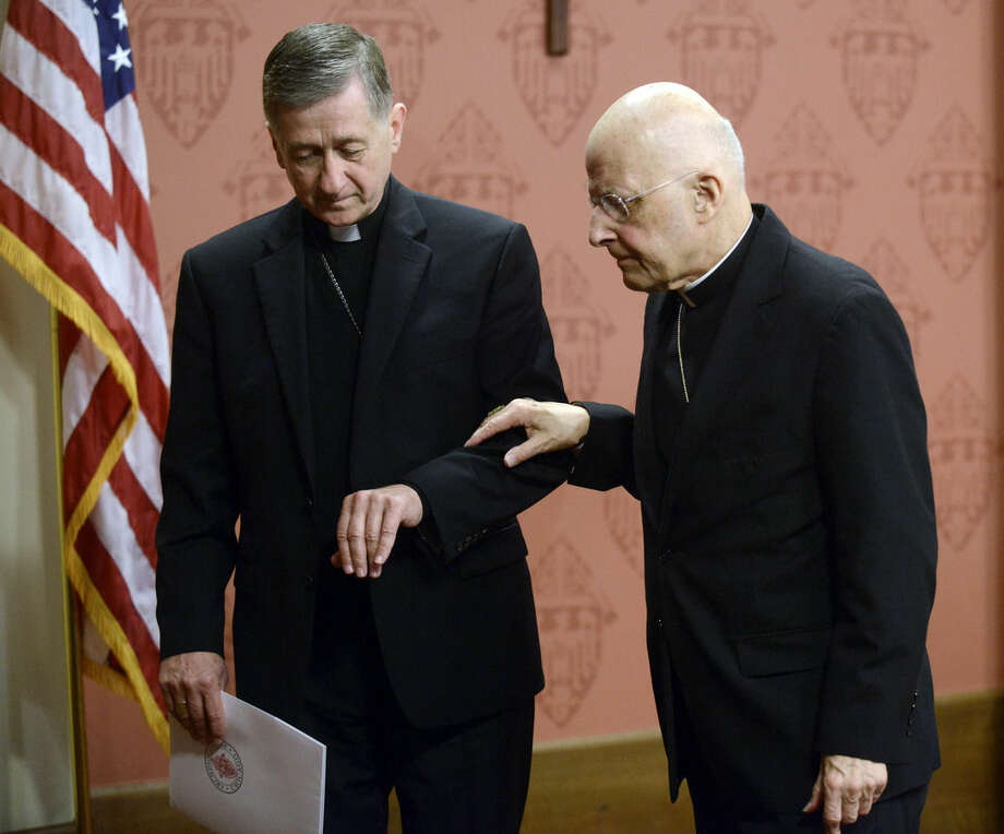 FILE - In this Sept. 20, 2014. file photo, Cardinal Francis George, right, retiring leader of the Archdiocese of Chicago right, walks away from the podium with help from newly-appointed Archbishop of Chicago, Archbishop Blase Cupich left, after George spoke to the media during a press conference in Chicago. The Chicago archdiocese announced Friday, April 17, 2015, that George died after a long fight with cancer. He was 78. (AP Photo/Paul Beaty, File)