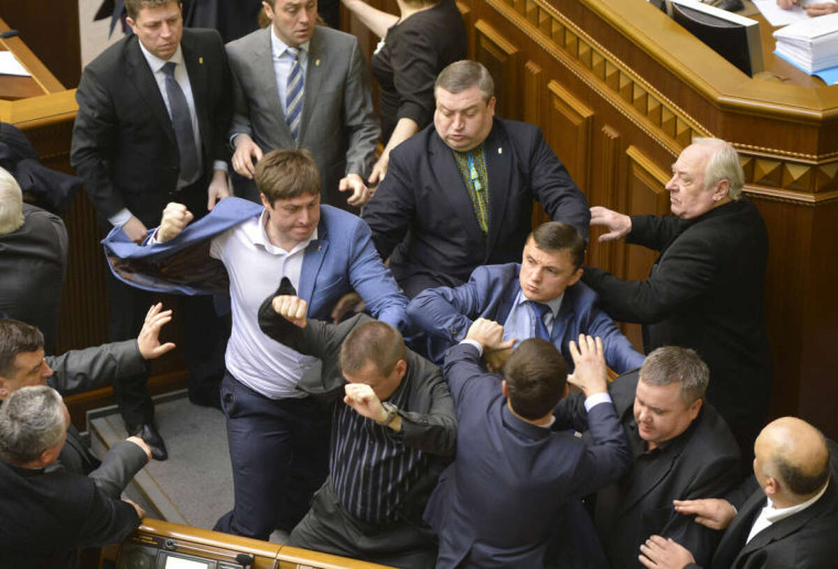Communist lawmakers scuffle with right-wing Svoboda (Freedom) Party lawmakers during a parliament session of Verkhovna Rada, the Ukrainian parliament, in Kiev, Ukraine on Tuesday, April 8, 2014. (AP Photo/Vladimir Strumkovsky)
