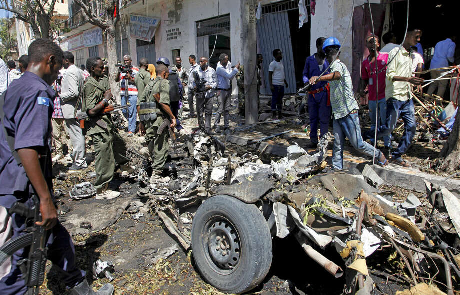 Security forces and others inspect the scene of a car bomb attack in the capital Mogadishu, Somalia Monday, April 11, 2016. A car bomb exploded outside a restaurant packed with lunchtime customers, killing at least five people according to witnesses in the capital's Hamarweyne district, close to the municipal government headquarters and a busy commercial area. (AP Photo/Farah Abdi Warsameh)