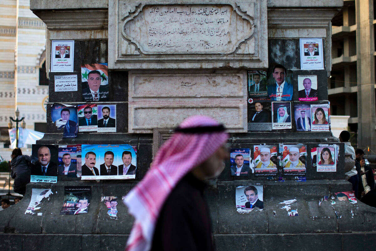 Syrians pass by campaign posters for parliamentary candidates as they gather in the Marjeh square in Damascus , Syria, Monday, April 11, 2016. The vote - expected to be a rubber stamp of President Bashar Assad's loyalists - will only proceed in government-controlled areas as the Damascus authorities are unable to organize any balloting in rebel-controlled areas or the territory under the Islamic State group. (AP Photo/Hassan Ammar)