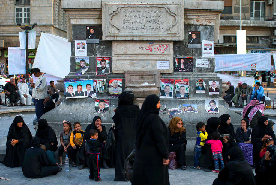 Syrians sit in front of campaign posters for parliamentary candidates as they gather in the Marjeh square in Damascus , Syria, Monday, April 11, 2016. The vote - expected to be a rubber stamp of President Bashar Assad's loyalists - will only proceed in government-controlled areas as the Damascus authorities are unable to organize any balloting in rebel-controlled areas or the territory under the Islamic State group. (AP Photo/Hassan Ammar)