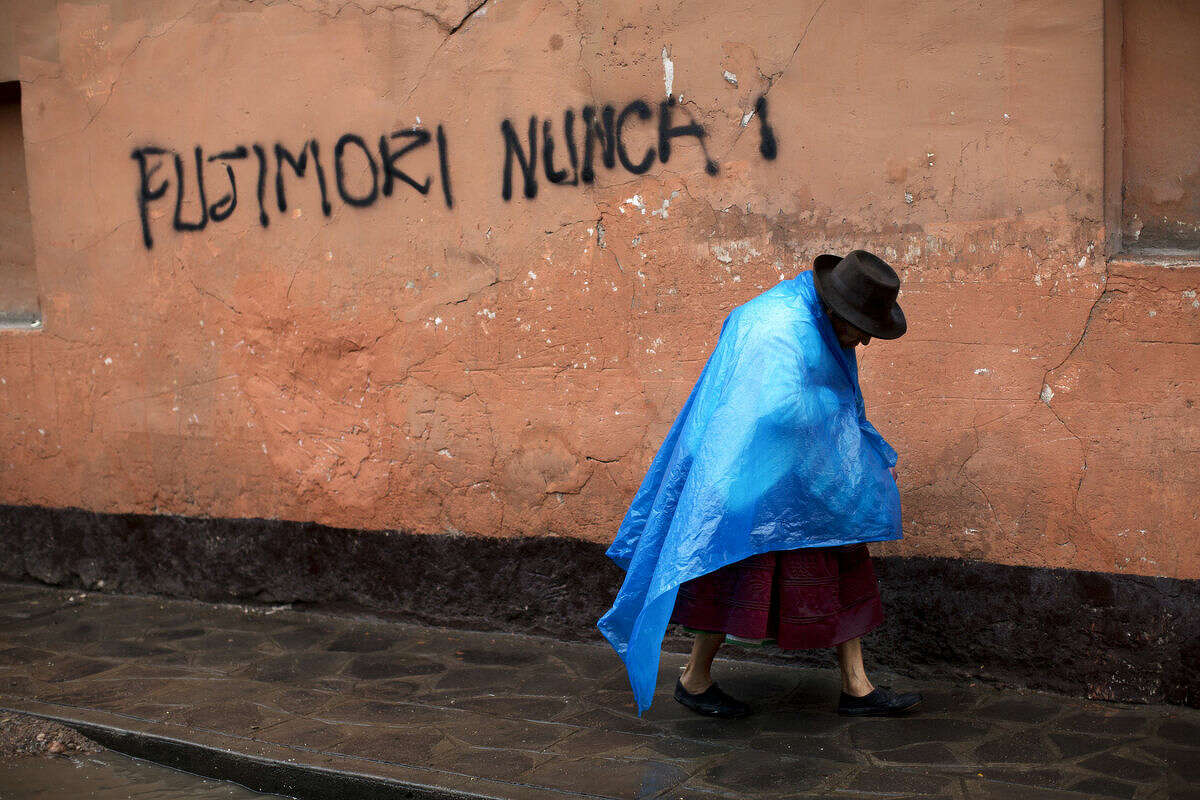 """A Quechua Indian woman walks next to a graffiti that reads in Spanish """"Fujimori never!"""" in Ayacucho, Peru, Monday, April 11, 2016. Keiko Fujimori, the daughter of jailed former President Alberto Fujimori won the first round of the presidential elections and will face Pedro Pablo Kuczynski of the """"Peruanos por el Kambio"""" political party in a June runoff. (AP Photo/Rodrigo Abd)"""