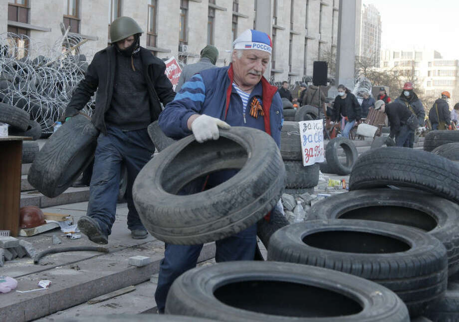Activists prepare a barricade in front of the regional administration building in Donetsk, Ukraine, Tuesday, April 8, 2014. Ukrainian authorities on Tuesday reasserted control over an administration building in Kharkiv, the country's second-largest city, which had been seized by pro-Russian protesters, detaining dozens. Meanwhile, in Donetsk, a city 250 kilometers (155 miles) further south, the makings of an improved self-appointed government began taking shape as demonstrators dug in for their third day at the 11-story regional administration headquarters. (AP Photo/Efrem Lukatsky)