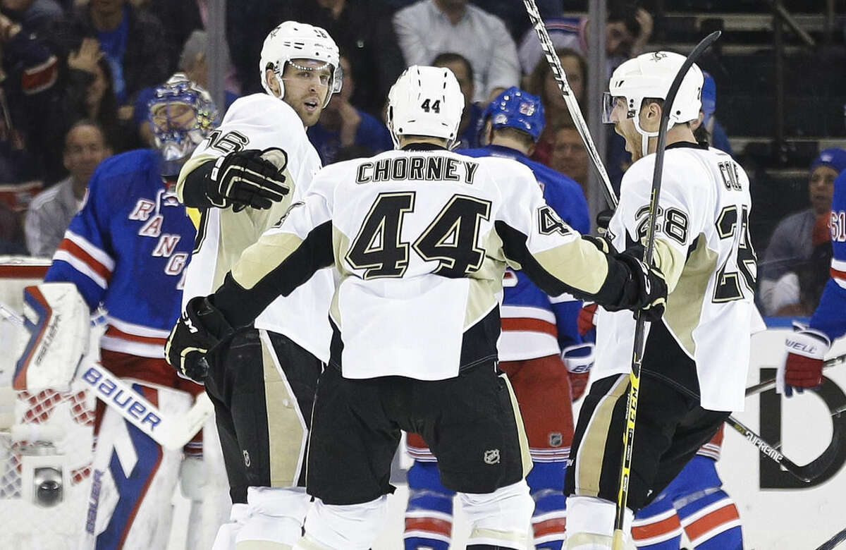 Pittsburgh Penguins' Brandon Sutter, second from left, celebrates with teammates after scoring a goal against New York Rangers goalie Henrik Lundqvist, left, of Sweden, during the second period of Game 2 in the first round of the NHL hockey Stanley Cup playoffs Saturday, April 18, 2015, in New York. (AP Photo/Frank Franklin II)