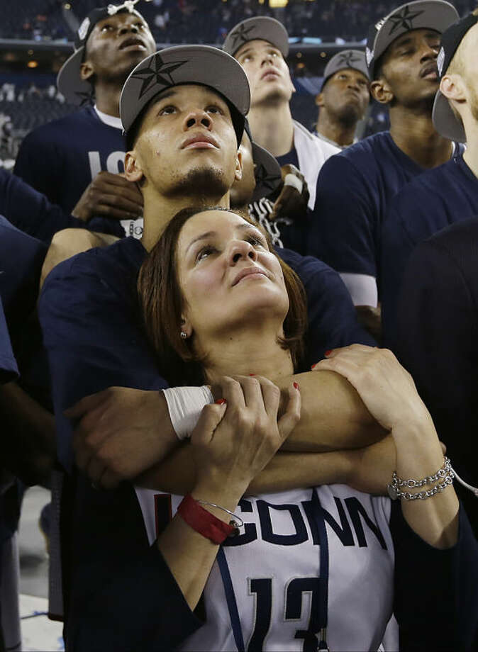 Connecticut guard Shabazz Napier embraces his mother, Carmen Velasquez as the team watches a highlight video of March Madness after their team beat Kentucky, 60-54 at the NCAA Final Four tournament college basketball championship game Monday, April 7, 2014, in Arlington, Texas. (AP Photo/David J. Phillip)