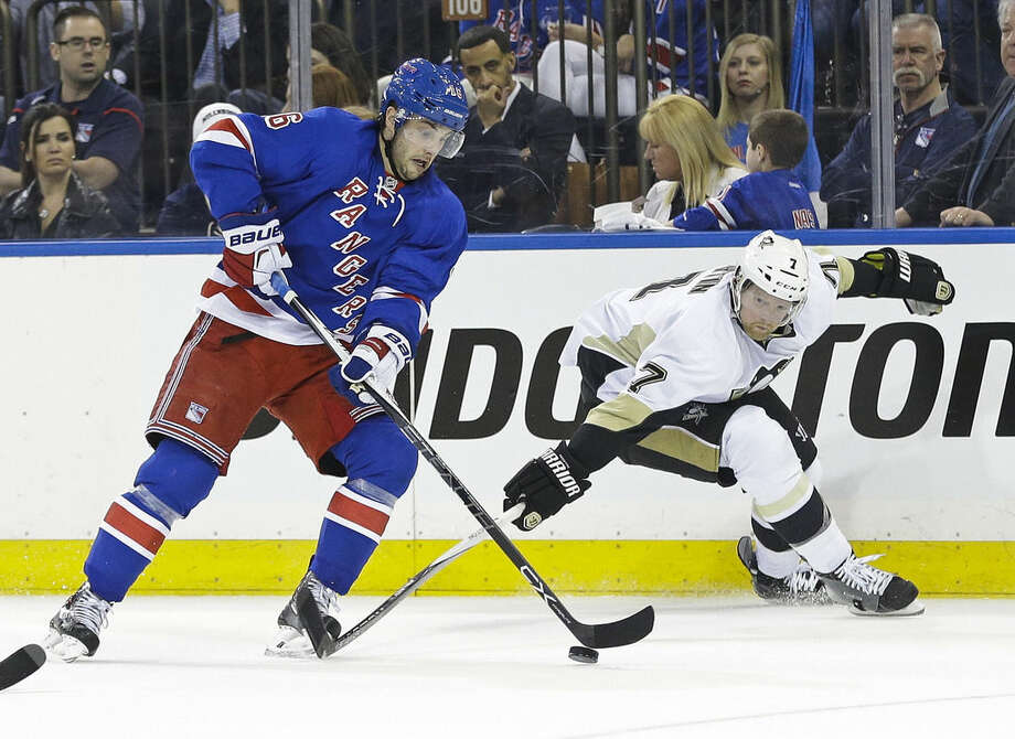 Pittsburgh Penguins' Paul Martin (7) fights for control of the puck with New York Rangers' Derick Brassard (16) during the second period of Game 2 in the first round of the NHL hockey Stanley Cup playoffs Saturday, April 18, 2015, in New York. (AP Photo/Frank Franklin II)