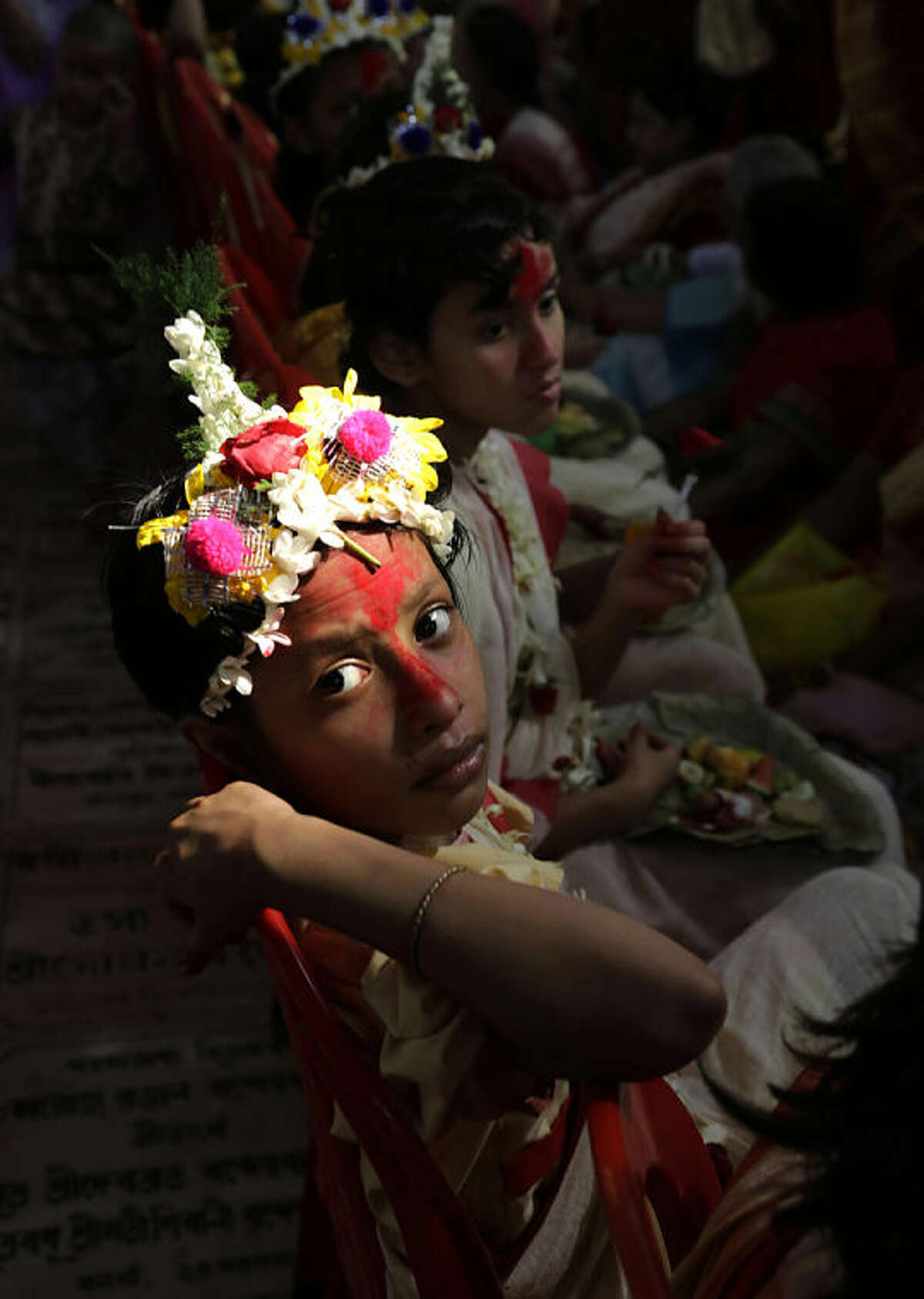 """A young girl Hindu girl dressed as """"Kumari,"""" or a living goddess, looks up as she is worshipped by devotees during the Hindu festival of Ram Navami, in Kolkata, India, Tuesday, April 8, 2014. (AP Photo /Bikas Das)"""