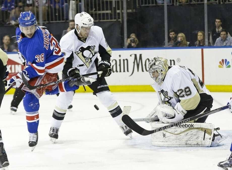 Pittsburgh Penguins goalie Marc-Andre Fleury (29) stops a shot on goal as teammate Ben Lovejoy (12) and New York Rangers' Mats Zuccarello (36) watch during the second period of Game 2 in the first round of the NHL hockey Stanley Cup playoffs Saturday, April 18, 2015, in New York. (AP Photo/Frank Franklin II)