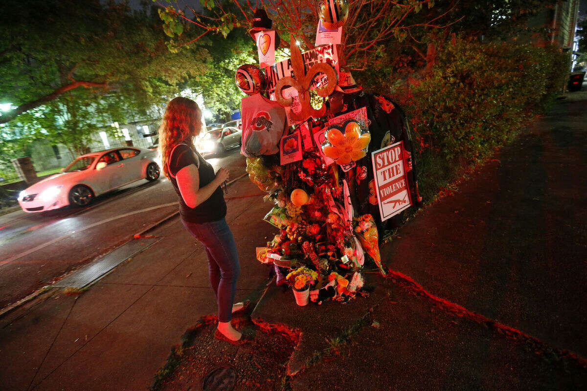 Jacquelyn Brubaker, of New Orleans, looks at a makeshift memorial Monday, April 11, 2016, near the spot where former New Orleans Saints defensive end Will Smith was shot and killed, and his wife was wounded by gunfire, after a traffic accident in New Orleans on Saturday. (AP Photo/Gerald Herbert)