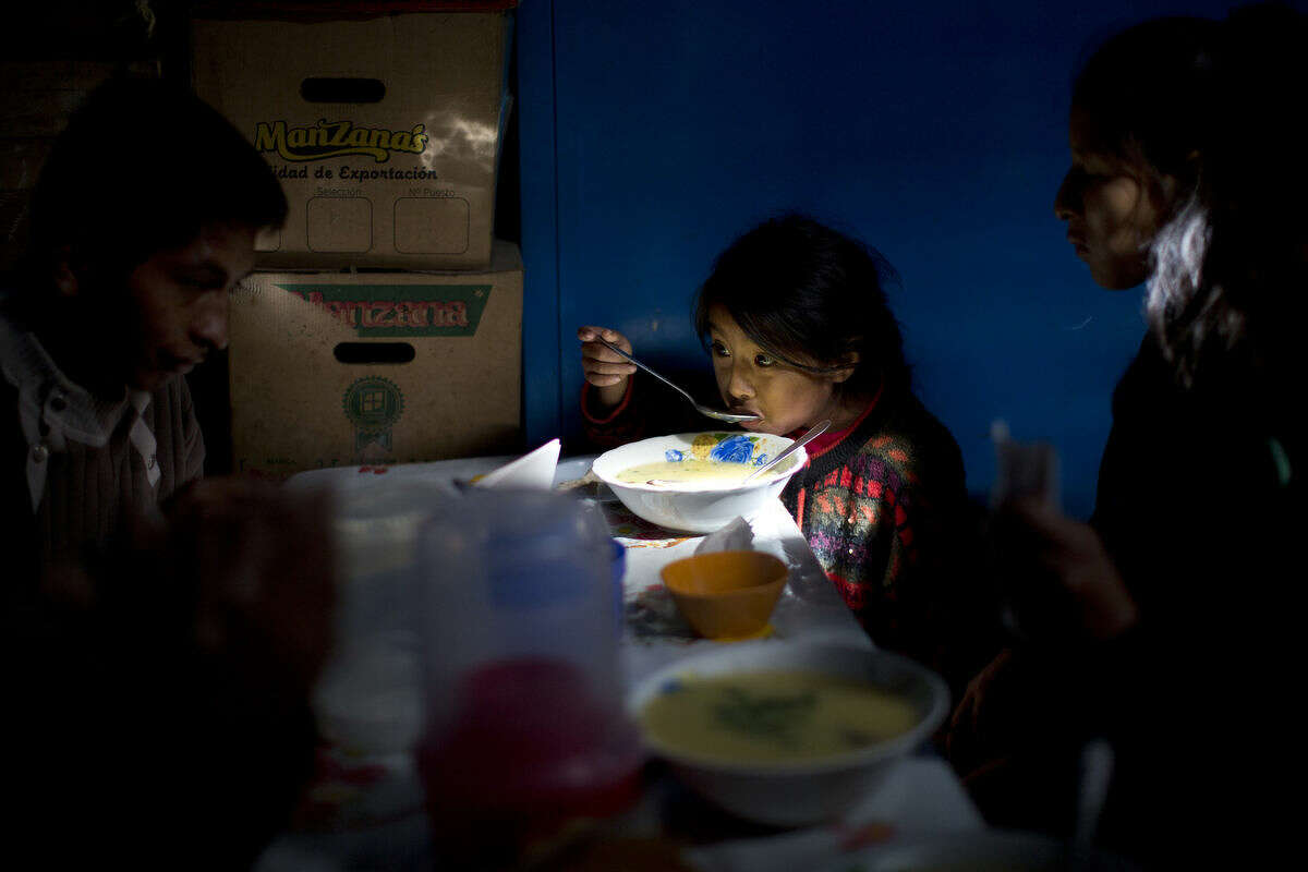 """Dalia, 6, eats corn soup for breakfast at the central market a day after general elections were held, in Ayacucho, Peru, Monday, April 11, 2016. Keiko Fujimori, the daughter of jailed former President Alberto Fujimori won the first round of the presidential elections and will face Pedro Pablo Kuczynski of the """"Peruanos por el Kambio"""" political party in a June runoff. (AP Photo/Rodrigo Abd)"""