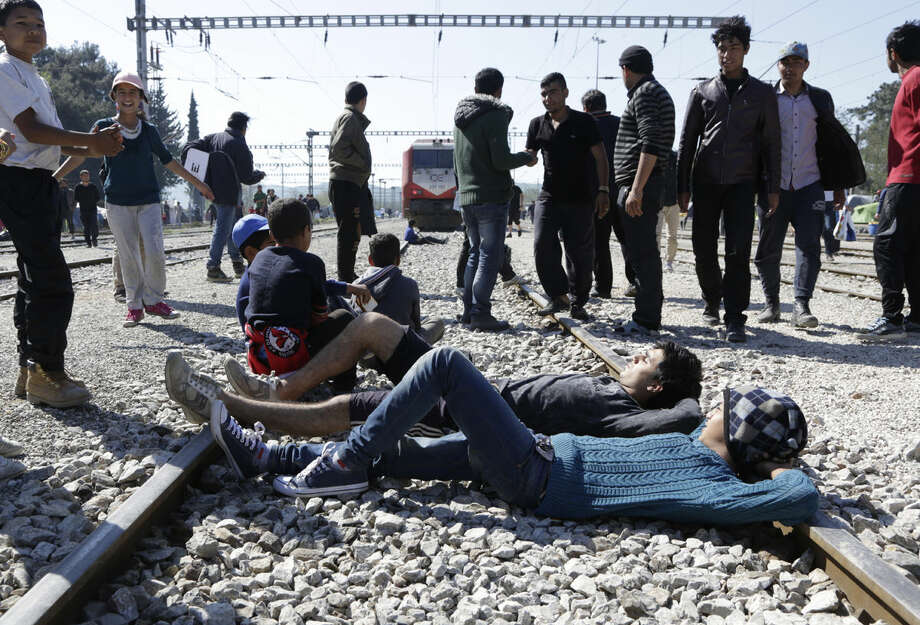 Men lay across the rail tracks preventing a Greece locomotive to drive away a cargo wagon at the makeshift camp at the northern Greek border point of Idomeni, Greece, Tuesday, April 12, 2016. More than 12,000 people have been stuck here for more than a month with hopes that the border would reopen. (AP Photo/Amel Emric)