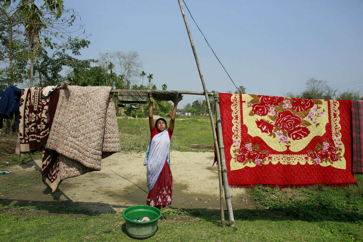 An Indian village woman dries clothes near her house at Panbari village the Duke and Duchess of Cambridge are expected to visit near Kaziranga National Park, east of Gauhati, northeastern Assam state, India, Tuesday, April 12, 2016. The British royal couple is visiting the wildlife park specifically to focus global attention on conservation. The 480-square-kilometer (185-square-mile) grassland park is home to the world's largest population of rare, one-horned rhinos as well as other endangered species, including swamp deer and the Hoolock gibbon. (AP Photo/ Anupam Nath)