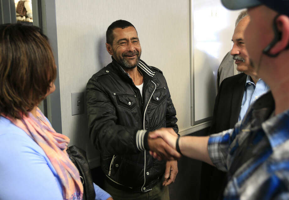 """Ahmad al-Abboud, center, shakes hands with a reporter following a news conference at Della Lamb Community Services in Kansas City, Mo., Monday, April 11, 2016. Ahmad al-Abboud and his family are the first Syrian family to be resettled in the U.S. under a speeded-up """"surge operation"""" for refugees. (AP Photo/Orlin Wagner)"""