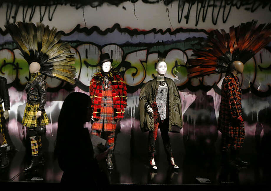 A visitor looks at the creations of French couturier Jean Paul Gaultier during the launch of his exhibition 'The Fashion World of Jean Paul Gaultier : From the Sidewalk to the Catwalk' at the Barbican Art Gallery in London, Tuesday, April 8, 2014. (AP Photo/Sang Tan)
