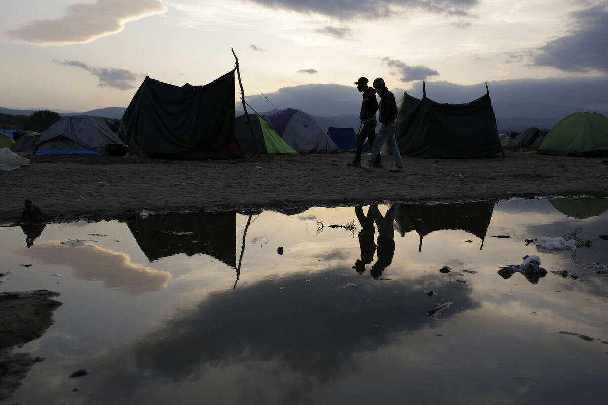 Migrant men are reflected in a pond as they walk among tents, at the makeshift camp at the northern Greek border point of Idomeni, Greece, Monday, April 11, 2016. More than 12,000 people have been stuck her for more than a month amid hopes that the border would reopen. (AP Photo/Amel Emric)