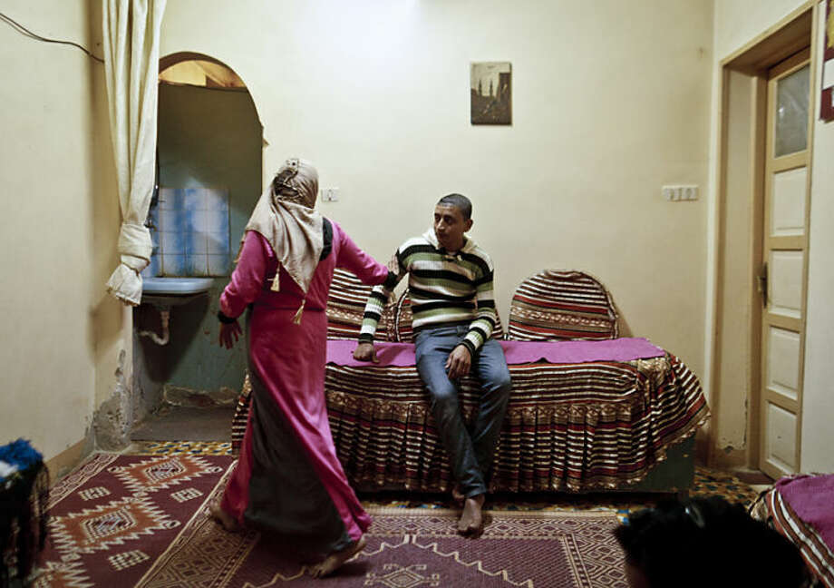 In this Monday, Dec. 10, 2012 photo, Dunia, 15, passes her fiancee at her family's apartment in Beheira, Egypt. The couple, who are cousins, married a few months later. Women activists say they won a major step forward with Egypt's new constitution, which enshrined greater rights for women. But months after its passage, they're worrying whether those rights will be implemented or will turn out to be merely ink on paper. Men hold an overwhelming lock on decision-making and are doing little to bring equality, activists say, and the increasingly repressive political climate is stifling chances for reforms. (AP Photo/Maya Alleruzzo) EGYPT OUT