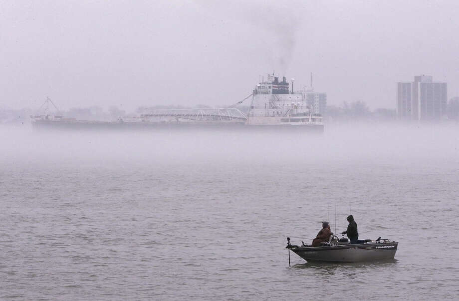 Fishermen cast their lines in the Detroit River as the Sam Laud, an iron ore freighter, travels through the fog, Monday, April 11, 2016, in Detroit. (AP Photo/Carlos Osorio)