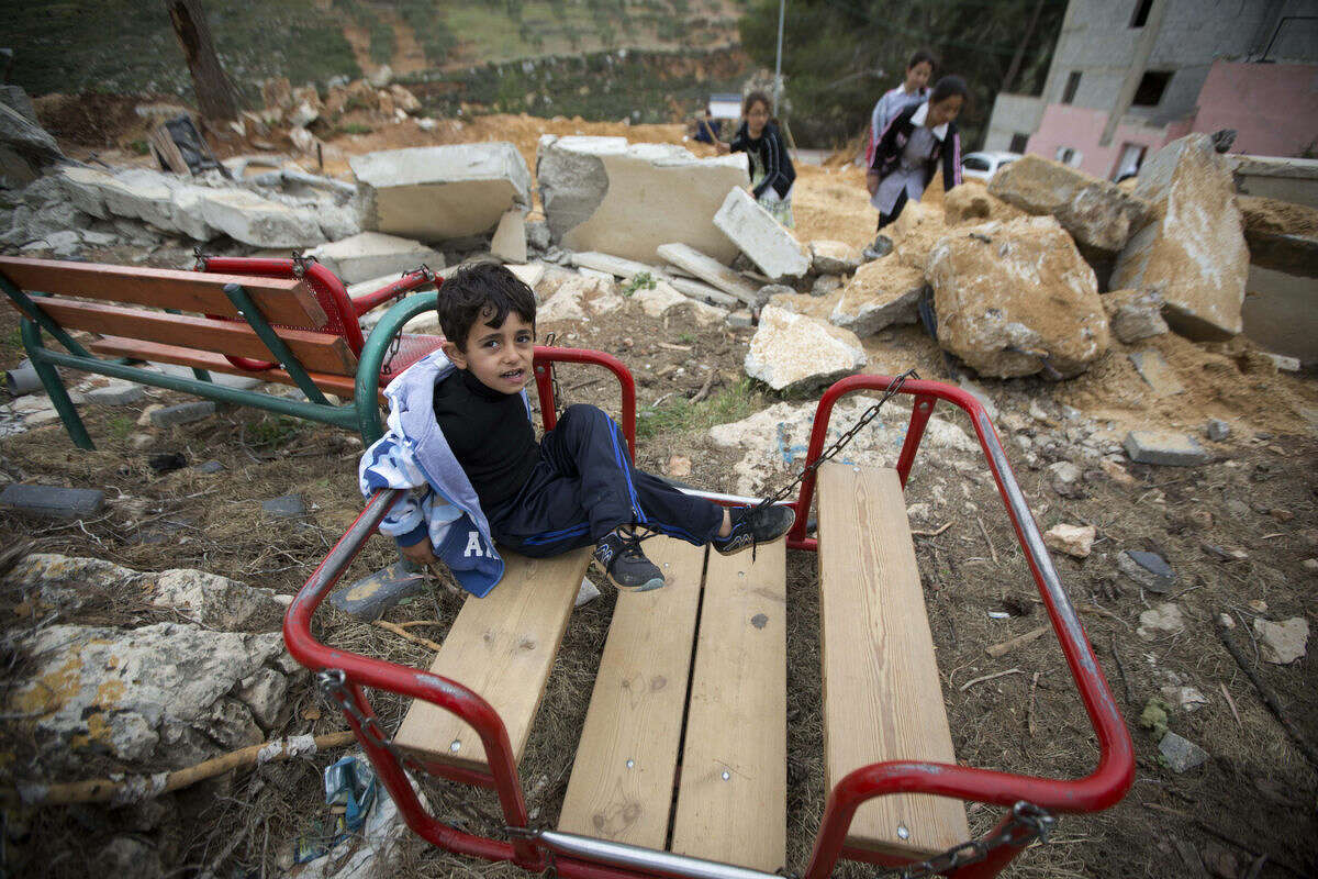 A Palestinian boy sits in the ruins of a children's garden after it was demolished by Israeli troops in the village of Za'tara near the West Bank city of Nablus, Tuesday, April 12, 2016. Israeli forces demolished the children's garden which was built 11 months ago because it was erected without permission, it was funded by the Belgian Development Agency. (AP Photo/Majdi Mohammed)