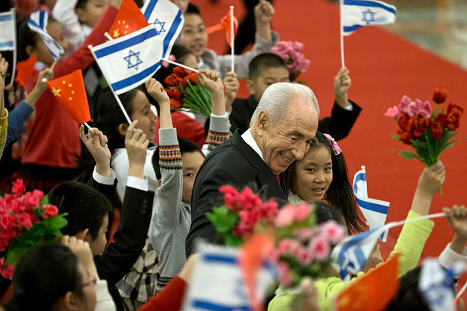 Israeli President Shimon Peres, center, hugs Chinese children during a welcome ceremony held by Chinese president Xi Jinping at the Great Hall of the People in Beijing Tuesday, April 8, 2014. (AP Photo/Alexander F. Yuan)