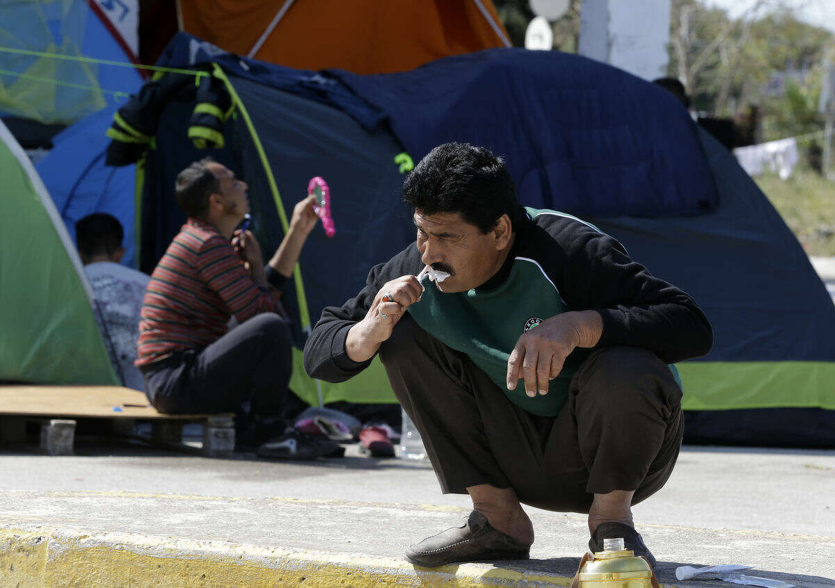 An Afghan man brushes his teeth as another one shave at the old international airport, which is used as a shelter for over 4,300 refugees and migrants, in southern Athens, on Tuesday, April 12, 2016. More than 53,000 people who made their way to Greece from Turkey have been stranded in the country since Balkan and European nations shut their land borders to stem the largest refugee flow the continent has seen since World War II. (AP Photo/Thanassis Stavrakis)