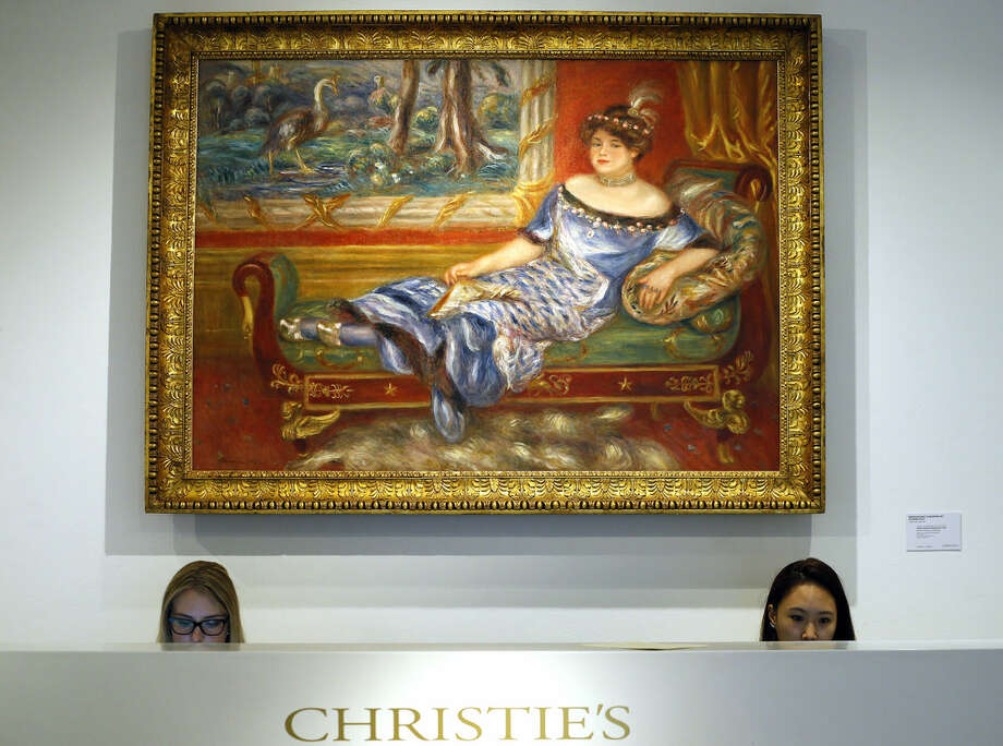 Christie's employees sit at the desk under a Pierre-Auguste Renoir painting called 'Madame de Galea a la meridienne' at Christies's auction rooms in London, Monday, April 11, 2016. The painting is estimated to realise 8-12 million US dollars (5.69-8.53 million UK pounds) when it is auctioned in New York in the Impressionist and Modern Art sale on May 12. (AP Photo/Kirsty Wigglesworth)