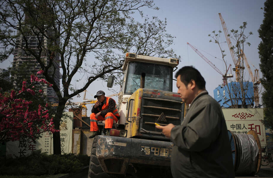 A man walks past a worker smoking on a bulldozer parked by a construction site at the Central Business District in Beijing, Monday, April 11, 2016. China will remain the main driver of growth in Asia this year despite its prolonged slowdown, helped by sustained expansions in other developing countries in the region, the World Bank said Monday. (AP Photo/Andy Wong)