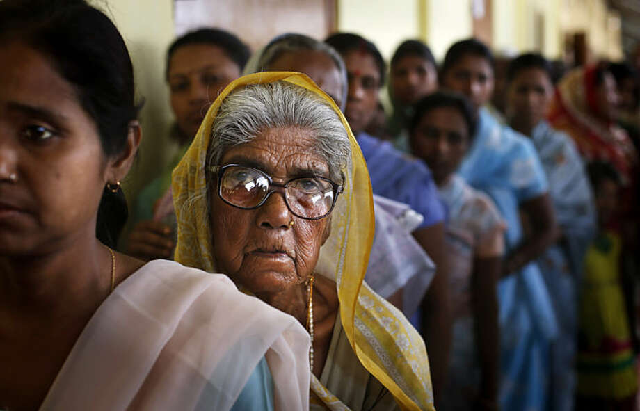An elderly Indian woman watches as she stands in a queue to cast her vote during the first phase of elections in Dibrugarh, in the northeastern state of Assam, India, Monday, April 7, 2014. India started the world's largest election Monday, sealing international borders along its remote northeast while voters made their way past lush rice paddies and over rickety bamboo bridges and pot-holed dirt roads to reach the polls. The country's 814 million eligible voters will vote in stages over the next five weeks. (AP Photo/Altaf Qadri)