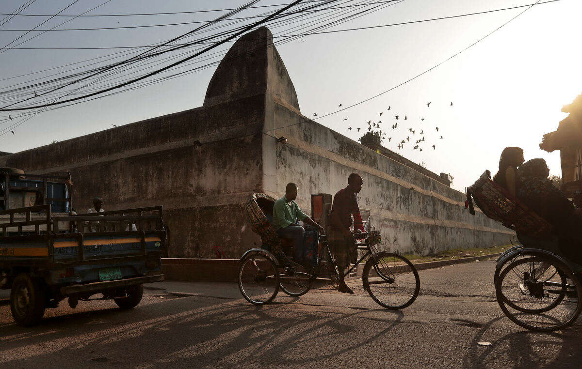 In this April 10, 2016 photo, people commute on a road next to the Dhaka Central Jail in Dhaka, Bangladesh. The government wants to reopen the old, dilapidated Dhaka Central Jail as a museum to its tumultuous past, while giving its inmates better accommodations on the outskirts of Dhaka, the capital. The new jail will have an uninterrupted power supply, a 200-bed hospital and a job training center. (AP Photo/ A.M. Ahad)