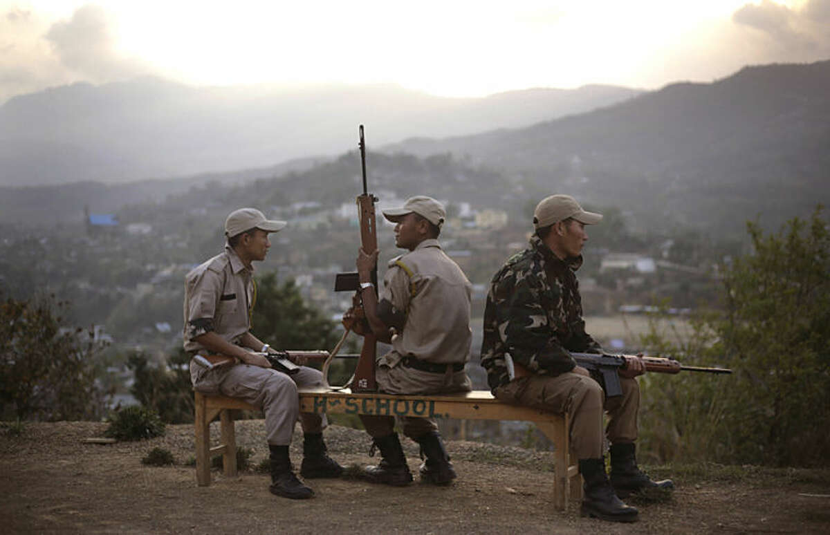 Indian security personnel sit on a school bench outside a make shift polling center in a school on the eve of the second phase of Indian parliamentary elections at Senapati, in north eastern Manipur state, India, Tuesday, April 8, 2014. India started the world's largest election Monday where the country's 814 million electorate will vote in stages over the next five weeks. (AP Photo/Anupam Nath)