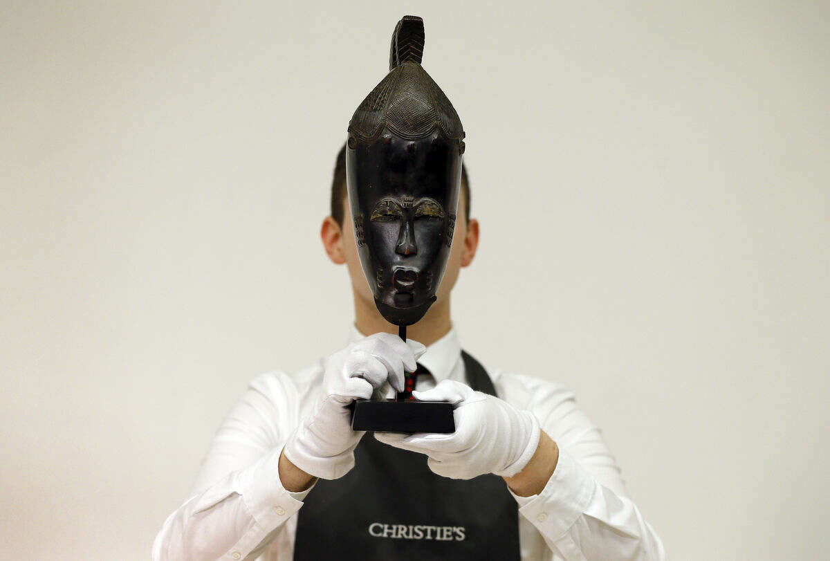 A Christie's employee holds 'The Mendes-France Baule Mask' from Ivory Coast at Christies's auction rooms in London, Monday, April 11, 2016. The mask is estimated to realise 500,000-800,000 US dollars (355,537-568,858 UK pounds) when it is auctioned in New York in the Evolution of Form : African and Oceanic Art at the Genesis of Modernism sale on May 12. (AP Photo/Kirsty Wigglesworth)