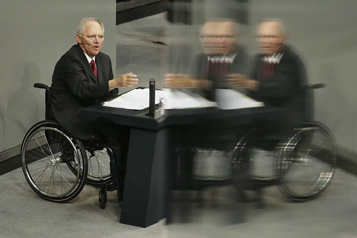 German Finance Minister Wolfgang Schaeuble delivers his speech during the first day of the debate about the German budget for 2014 at the parliament Bundestag in Berlin, Tuesday, April 8, 2014. On a four days debate the German parliament will discuss about the budget plans for the running year. The reflections from windows at the visitors tribune. (AP Photo/Markus Schreiber)