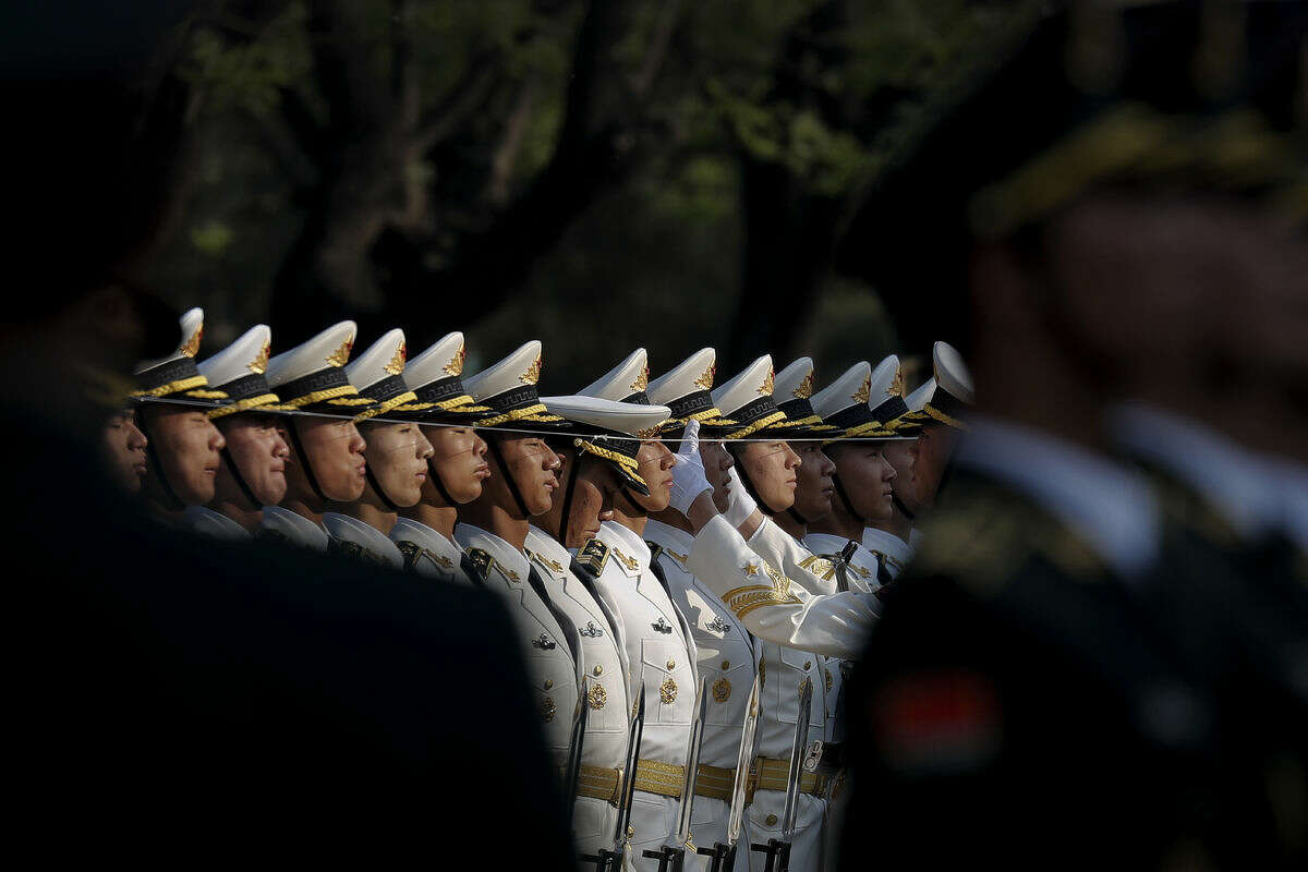 A Chinese People's Liberation Army soldier adjusts a hat of a member of an honor guard as they prepare for a welcome ceremony for visiting Nigeria's President Muhammadu Buhari outside the Great Hall of the People in Beijing, Tuesday, April 12, 2016. (AP Photo/Andy Wong)