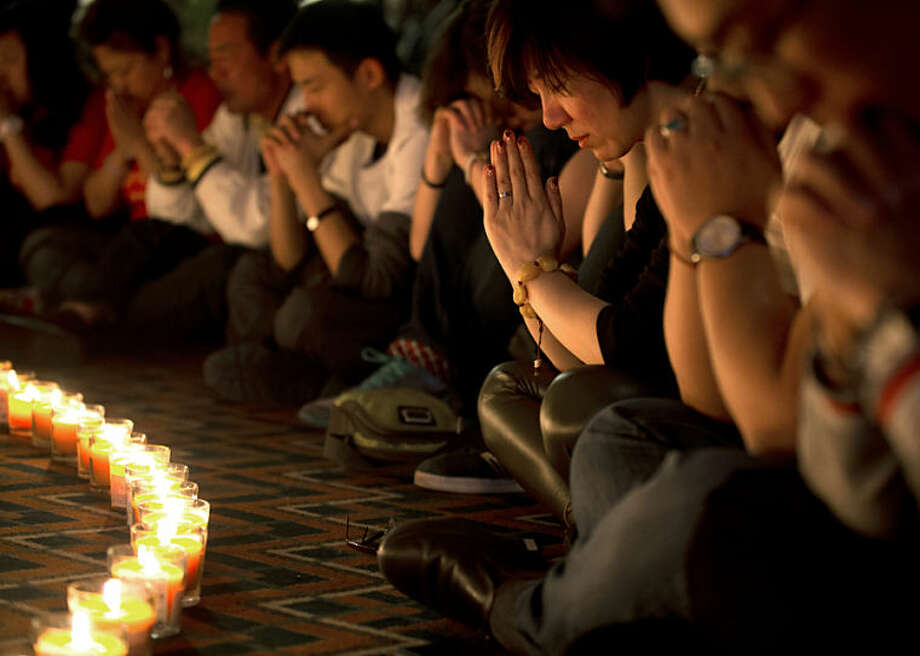 Relatives of Chinese passengers onboard Malaysia Airlines Flight 370 pray during a candlelight vigil for their loved ones at a hotel in Beijing, China, Tuesday, April 8, 2014. An Australian ship detected two distinct, long-lasting sounds underwater that are consistent with the pings from aircraft black boxes in a major break in the month long hunt for the missing Malaysia Airlines jet, the search coordinator said Monday, April 7, 2014. (AP Photo/Andy Wong)
