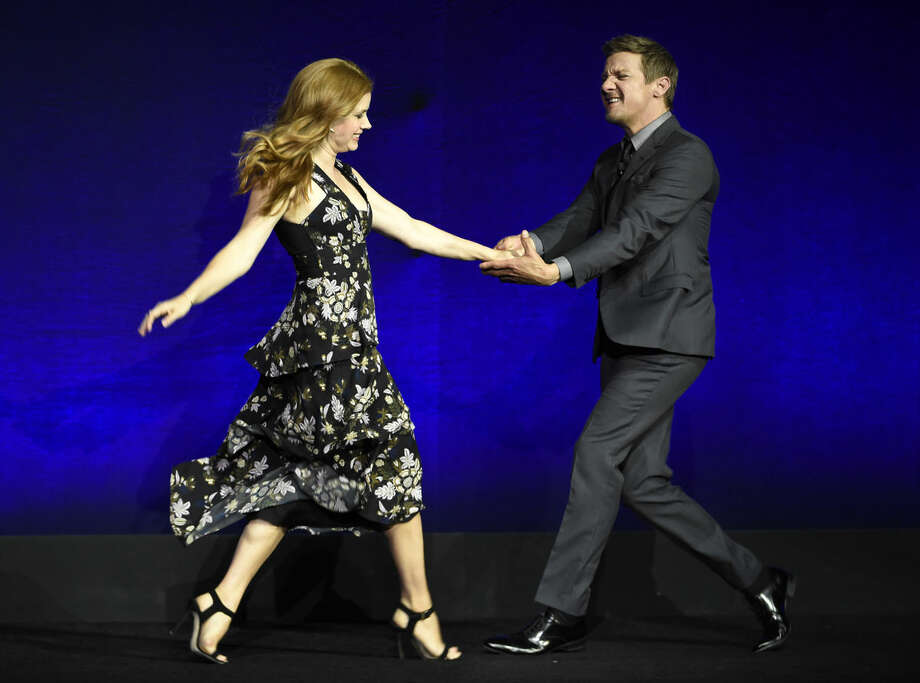 "Amy Adams, left, and Jeremy Renner, cast members in the upcoming film ""Story of Your Life,"" share a dance as they arrive onstage during the Paramount Pictures presentation at CinemaCon 2016, the official convention of the National Association of Theatre Owners (NATO), at Caesars Palace on Monday, April 11, 2016, in Las Vegas. (Photo by Chris Pizzello/Invision/AP)"