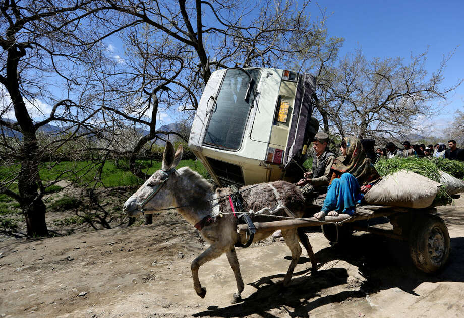 Afghan children travel on a donkey cart past the site of roadside bomb explosion on the outskirts of Kabul, Afghanistan, Monday, April 11, 2016. An Afghan official says at least one person has been killed when a bomb ripped through a bus carrying education ministry employees to work in the capital, Kabul. (AP Photo/Rahmat Gul)