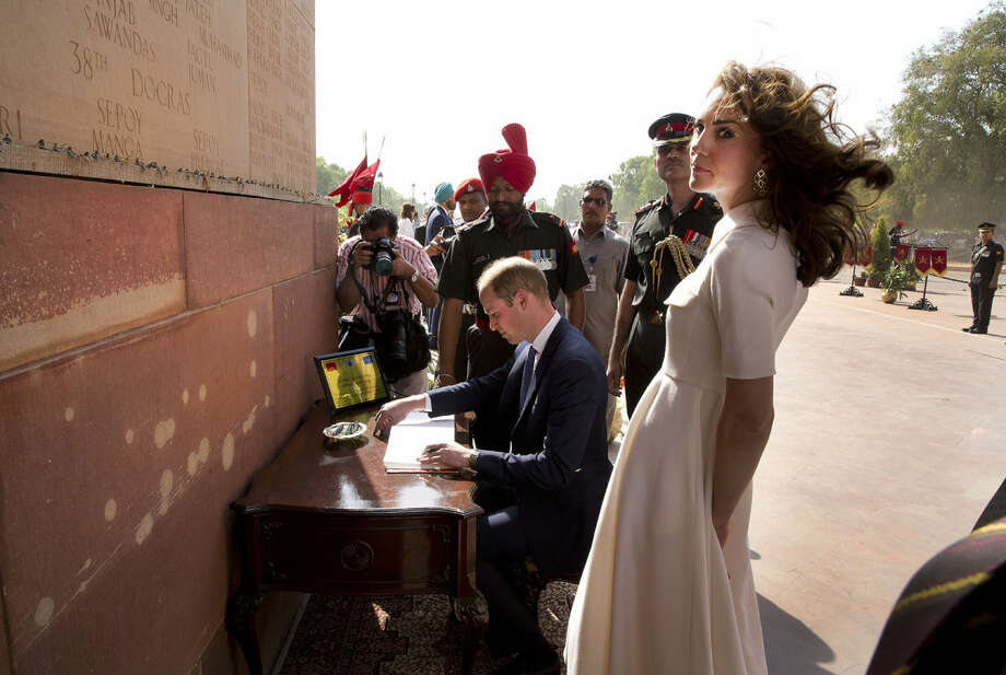 Britain's Prince William, signs visitor's book as his wife Kate, the Duchess of Cambridge looks on after paying their tributes at the India Gate war memorial, in the memory of the soldiers from Indian regiments who served in World War I, in New Delhi, India, Monday, April 11, 2016. (Manish Swarup/Pool Photo via AP)