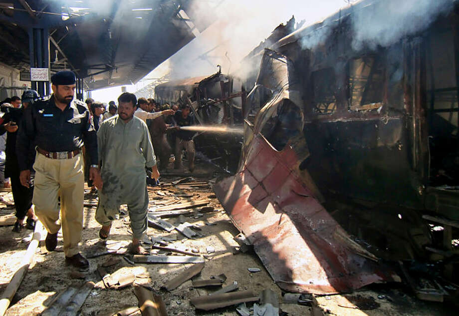 A Pakistani police officer investigates as firefighters try to extinguish a burning passenger train following an explosion in Sibi, Pakistan, Tuesday, April 8, 2014. A deadly bomb ripped through a railway car parked at a station in southwestern Pakistan, sending flames and smoke billowing into the air, officials said. (AP Photo/Saleem Gishkori)