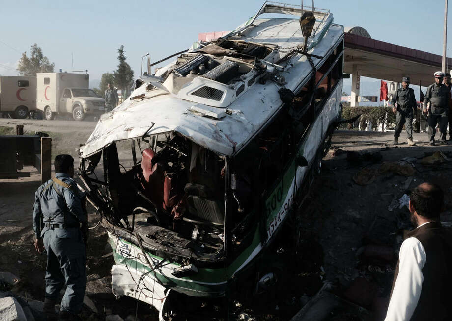 Afghans and security forces inspect damage to a bus after a suicide attack in Jalalabad east of Kabul, Afghanistan, Monday, April 11, 2016. An Afghan official says that at least 12 new army recruits have been killed in a suicide bomb attack in the eastern city of Jalalabad, Ahsanullah Shinwari, head of the Jalalabad hospital, said. (AP Photo/Mohammad Anwar Danishyar)