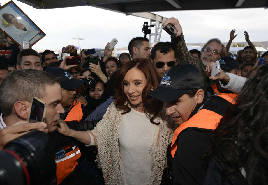 Argentina's former President Cristina Fernandez, center, arrives at the airport in El Calafate, Argentina, Monday, April 11, 2016. After spending four months in Patagonia, Fernandez traveled to Buenos Aires to attend a court summons to face questions about her government's handling of the futures dollar market. (AP Photo/Francisco Munoz)